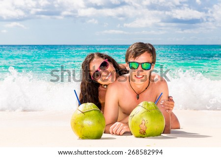 Young loving happy couple have fun on tropical beach, with coconuts. Summer vacation concept. - stock photo