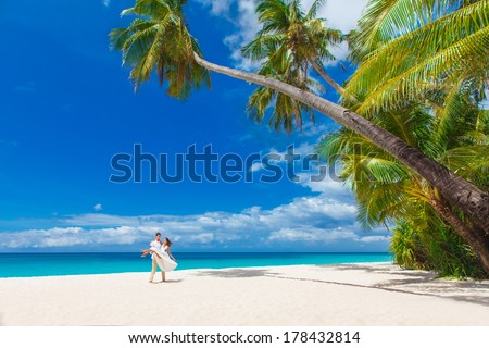 young loving happy couple on tropical beach with palm trees, wedding on beach - stock photo