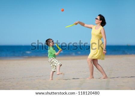 Young loving mother and her little son playing on the beach - stock photo
