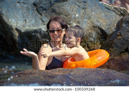 Young loving mother playing with her toddler son near a rocky seashore