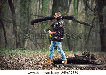Young lumberman in woods carrying log in one and axe in other hand  - stock photo