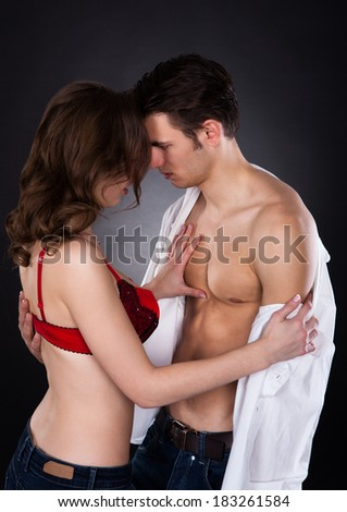 Young lusty woman in bra removing man's shirt isolated over black background - stock photo