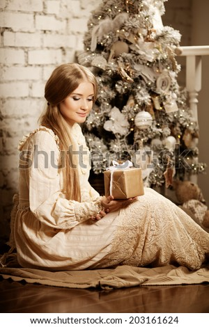 Young luxury vintage woman near Christmas tree with gift. Beautiful young girl celebrates Christmas in vintage style. - stock photo