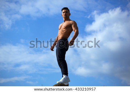 young macho man model athlete with muscular sexy body and bare chest posing outdoor on sky background