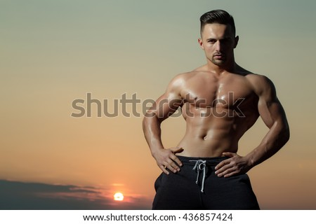 young macho man model athlete with muscular sexy body and wet bare chest outdoor on sky background