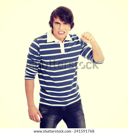 Young mad man with fist up - stock photo