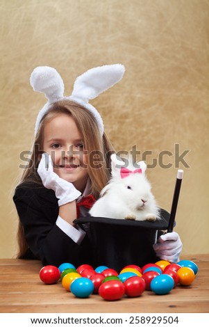Young magician after successfully conjuring an easter rabbit - sitting with satisfaction - stock photo