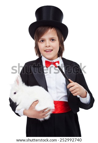 Young magician boy holding white rabbit and magic wand - isolated - stock photo