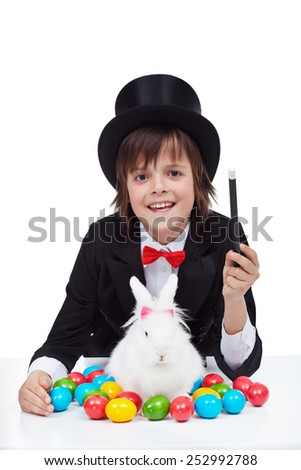Young magician boy preparing for easter - conjuring a white rabbit and colorful eggs - stock photo