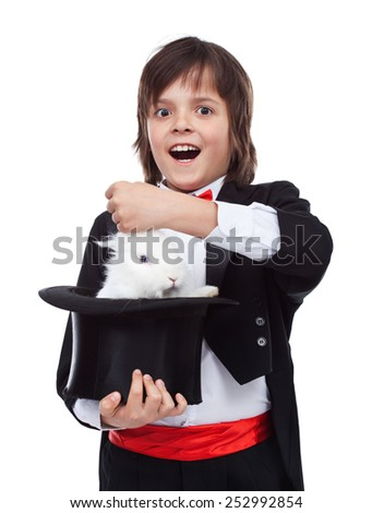 Young magician boy taking a cute white rabbit out of the hat - excited by his success - stock photo