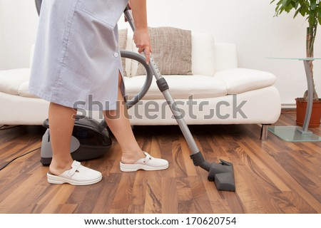 Young Maid Cleaning Floor With Handheld Vacuum Cleaner - stock photo