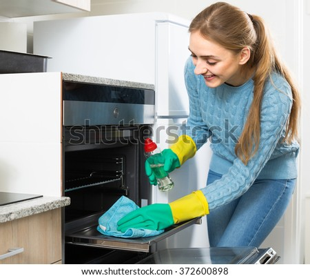 Young maid doing oven clean-up in domestic kitchen
