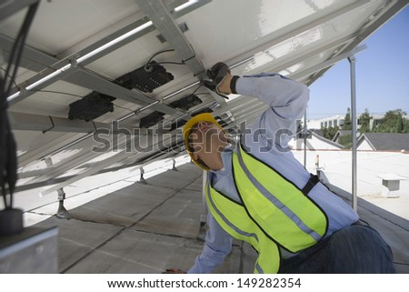 Young maintenance worker adjusting solar panels on rooftop - stock photo