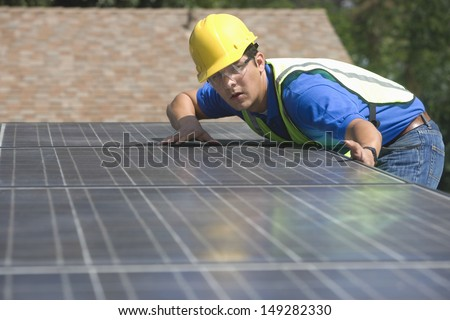 Young maintenance worker installing solar panels on rooftop - stock photo