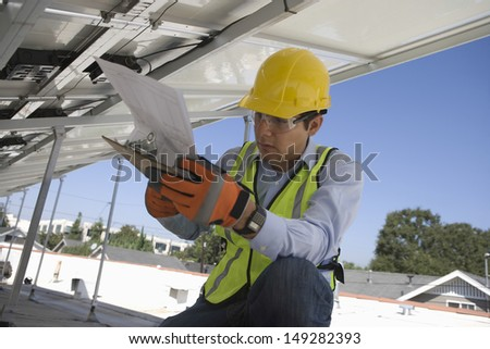 Young maintenance worker looking at clipboard under solar panels