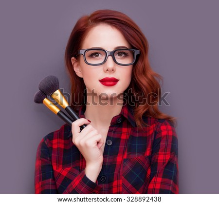 Young make-up artist with brushes on grey background