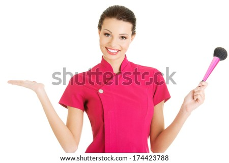 Young make-up artist woman showing copy space, isolated on white - stock photo