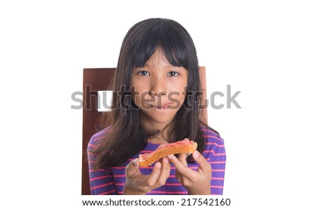 Young Malay Asian preteen girl having breakfast with bread and jam