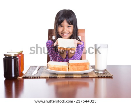 Young Malay Asian preteen girl having breakfast with bread and jam with a glass of milk