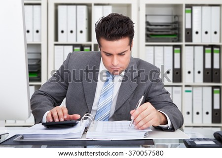 Young male accountant calculating bills at desk in office - stock photo