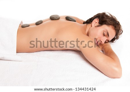young male adult receiving a hot stone massage laying down. studio shot isolated on white. - stock photo