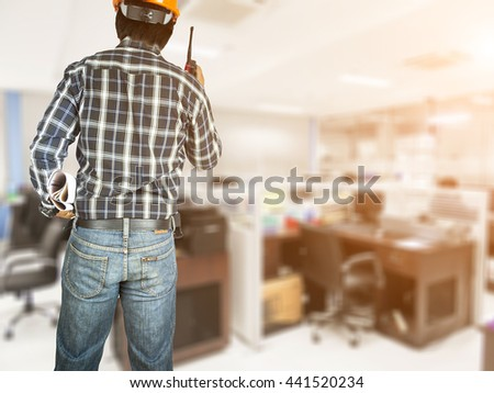 Young male architect/construction engineer at a room construction site - stock photo
