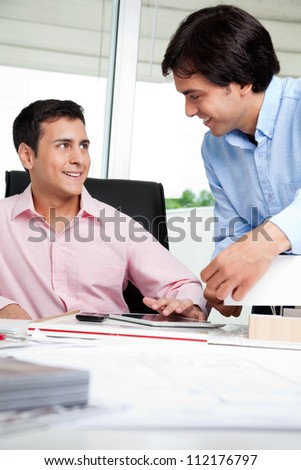 Young male architect looking at colleague while sitting in office chair