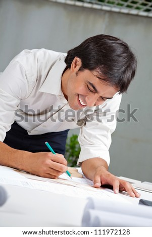 Young male architect smiling while working on blueprint