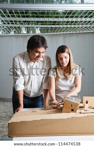 Young male architect standing beside colleague working on model house - stock photo