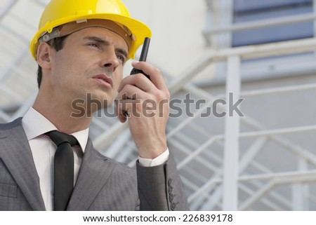 Young male architect talking on two-way radio against building - stock photo