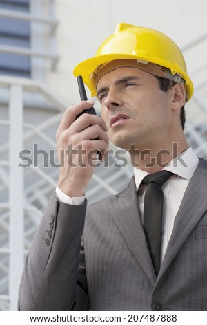 Young male architect talking on walkie-talkie against building - stock photo