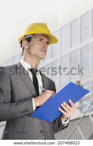 Young male architect writing on clipboard while looking away outside office building