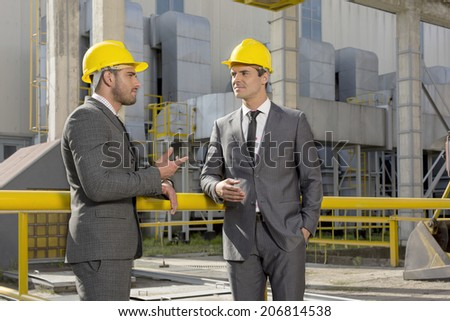 Young male architects discussing outside industry - stock photo