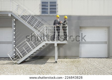 Young male architects with clipboard discussing on stairway - stock photo