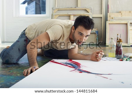 Young male artist looking at canvas on studio floor - stock photo