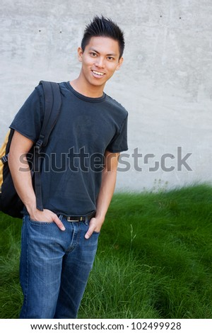 young male asian student standing outside with backpack - stock photo