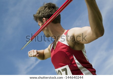 Young male athlete about to throw javelin against the sky - stock photo