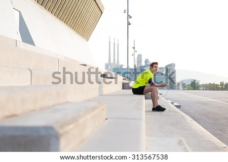 Young male athlete in bright sportswear resting after an active jogging while listening to music in headphones with copy space area, caucasian runner taking break after workout training outdoors - stock photo