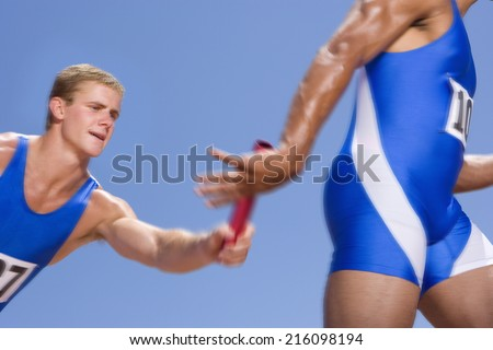 Young male athletes passing relay race baton - stock photo