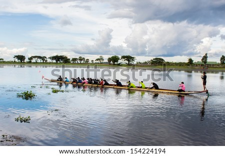 Young male athletes rowing boat on River - stock photo