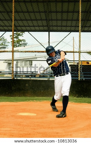 Young male baseball player connects with the pitch.  Ball line drives toward pitcher. - stock photo