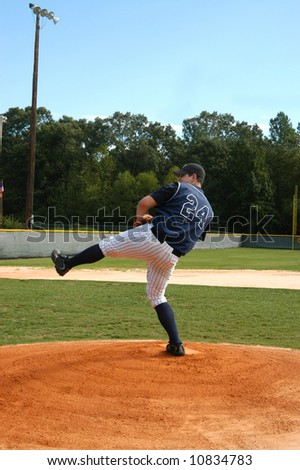 Young male baseball player winds up for the pitch.  Navy and white uniform.  Blue skies and baseball field. - stock photo