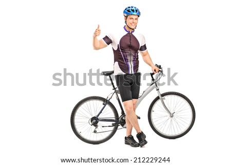 Young male biker giving a thumb up with his bicycle behind him isolated on white background