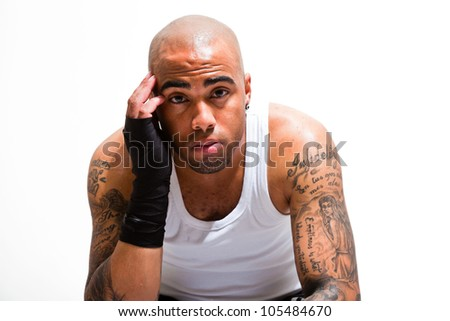 Young male boxer isolated on white background. Wearing white shirt and black shorts. Training outfit. Wet skin from sweating. Tattoos on his arms.