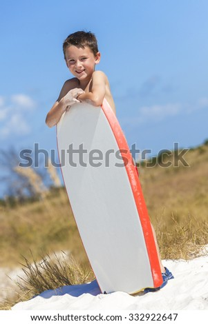 Young male boy child with white surfboard or boogie board on a beach with bright blue sky