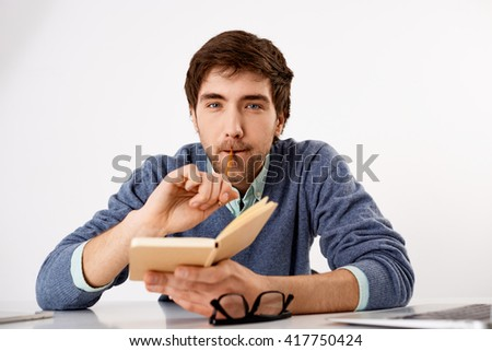 Young male business employee sitting at the desk and thinking with open notebook in hands looking at camera. Realistic and authentic situation at every office. - stock photo