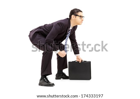 Young male businessman in sumo wrestling stance holding suitcase isolated on white background