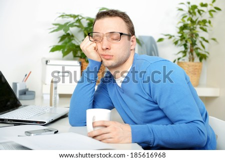young male businessman sitting in office and working - stock photo