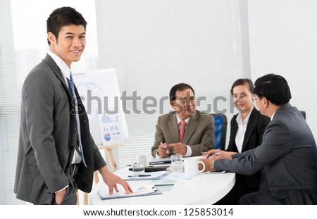 Young male businessman standing and looking at camera - stock photo