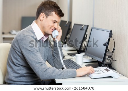 Young male call center employee using landline phone in office - stock photo